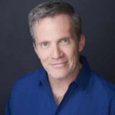 Headshot of Louis Bayard, a White man wearing a blue collared shirt