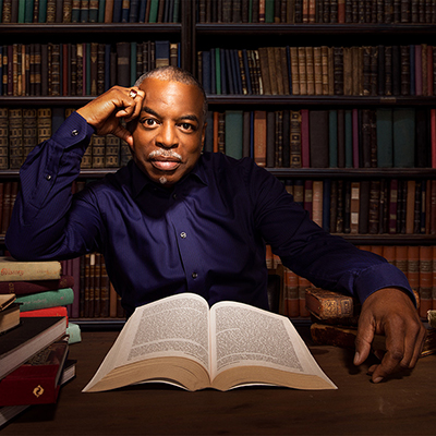 Headshot of LeVar Burton, a Black man in a dark blue collared shirt sitting at a desk in a library with a book open in front of him
