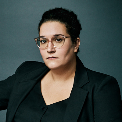 Headshot of author Carmen Maria Machado, a Latin woman wearing glasses and a black top and blazer
