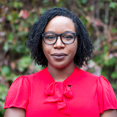 Headshot of author Lesley Nneka Arimah, a Black woman wearing glasses and a red top