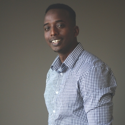 Headshot of Abdi Nor Iftin, a smiling Black man wearing a patterned button-down shirt