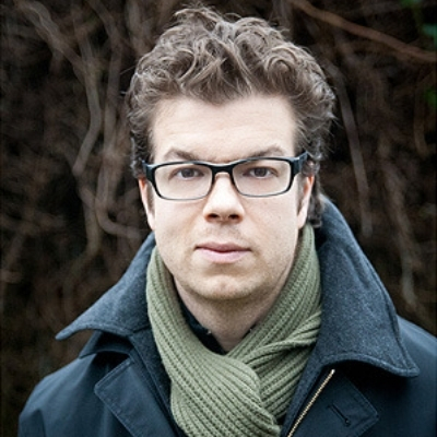 Headshot of author Ben Lerner, a White man wearing glasses, a green scarf, and a blue coat