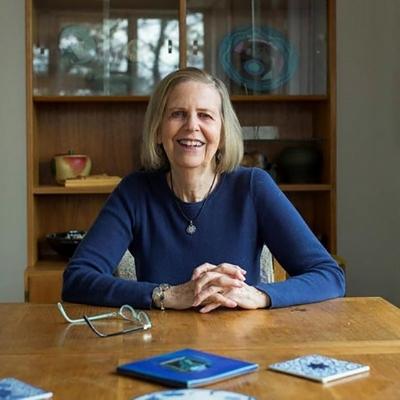 Headshot of author Bobbie Ann Mason, a smiling White woman wearing a blue long-sleeve shirt sitting at a desk