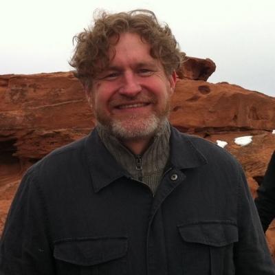 Headshot of author Brian Evenson, a smiling White man wearing a dark jacket