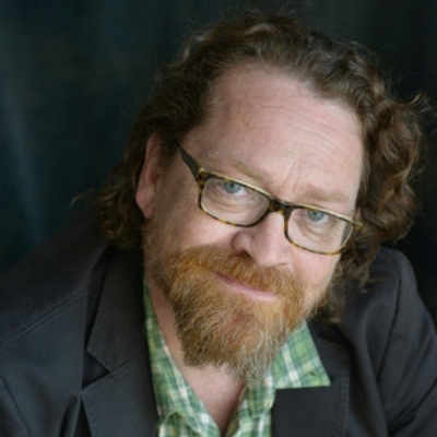 Headshot of author Dan Chaon, a White man with glasses and a beard wearing a green patterned shirt and a black blazer