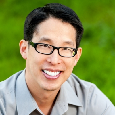 Headshot of writer Gene Luen Yang, a smiling Asian man wearing glasses and a gray collared shirt