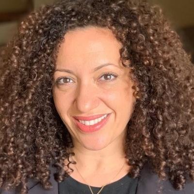 Headshot of Hannah Allam, a smiling Arab woman wearing a black jacket