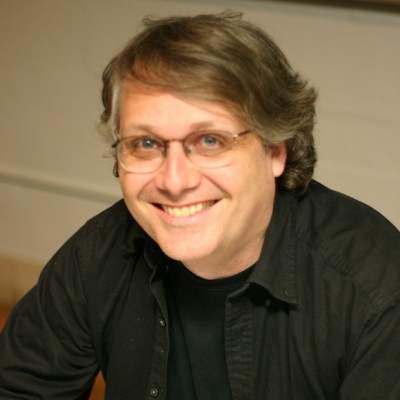 Headshot of writer Scott McCloud, a smiling White man wearing glasses and a dark collared shirt
