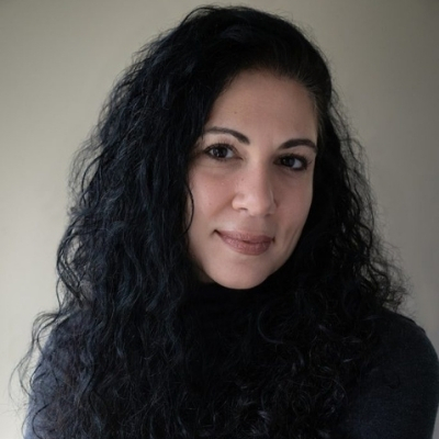 Headshot of author Susan Darraj, a smiling Arab woman with long curly hair wearing a black top
