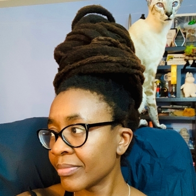 Headshot of author Nnedi Okorafor, a Black woman wearing glasses with a cat perched behind her