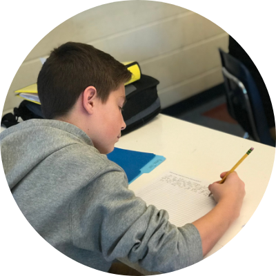 A male student in a gray sweatshirt writing on a piece of paper in a classroom