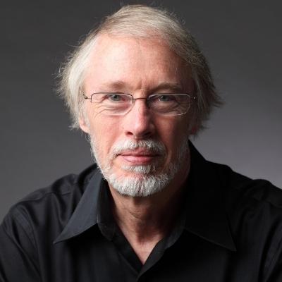 Headshot of writer Charles Baxter, a White man wearing glasses and a black shirt