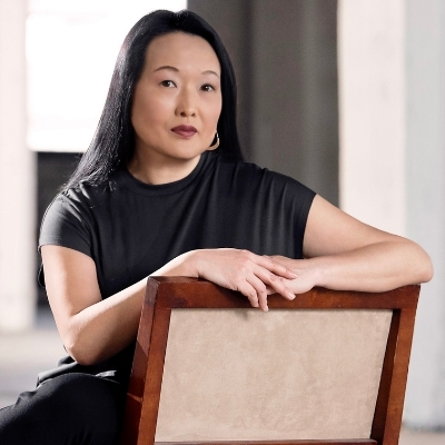 Headshot of Asian woman, Jung Yun, sitting on a chair with long black hair wearing gold dangly earrings and a black dress