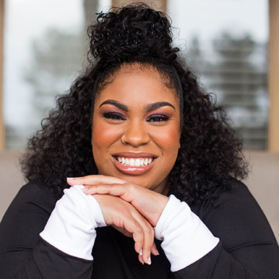 Headshot of author Angie Thomas, a smiling Black woman with a top knot wearing a black top