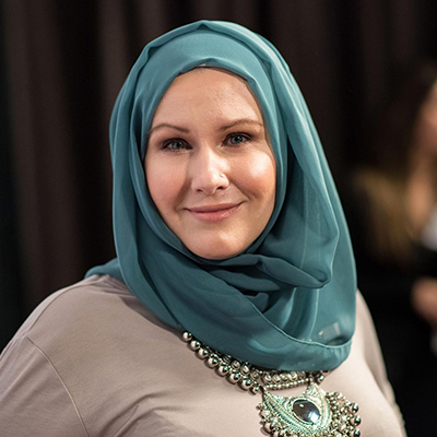Headshot of author G. Willow Wilson, a smiling woman wearing a blue headscarf and a gray top