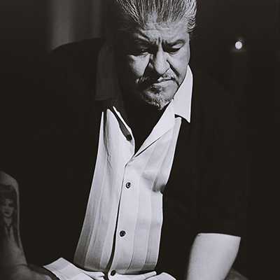 Black and white headshot of author Luis J. Rodriguez, a Xicanx person wearing a white collared shirt and black jacket