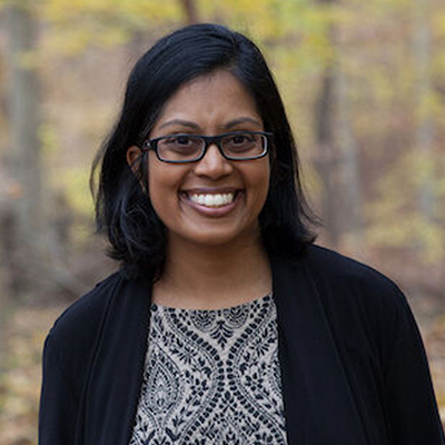 Headshot of author Mathangi Subramanian, a smiling South Asian woman wearing glasses and a black sweater