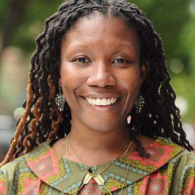 Headshot of author Nicole Dennis-Benn, a smiling Black woman wearing a colorful patterned top