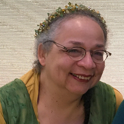 Headshot of author Nisi Shawl, a Black woman wearing glasses and a floral headband, smiling at the camera