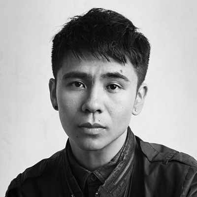 Black and white headshot of author Ocean Vuong, an Asian man wearing a dark jacket