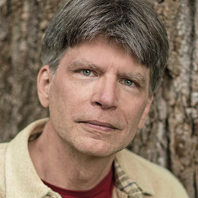 Headshot of author Richard Powers, a White man wearing a light collared top