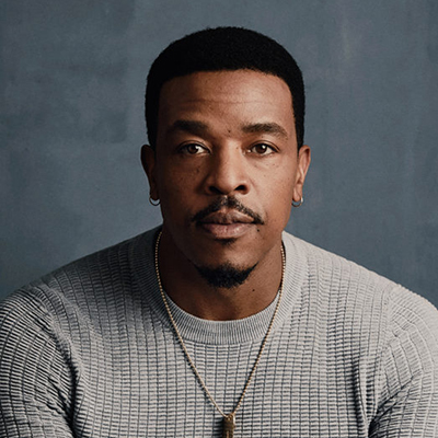 Headshot of actor Russell Hornsby, a Black man wearing earrings, a necklace, and a gray sweater
