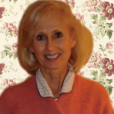 Headshot of Willee Lewis, a White woman wearing a pink sweater against a floral background