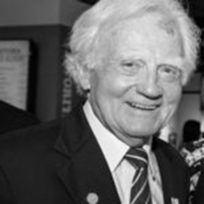 Black and white headshot of Malcolm O'Hagan, a White man in a suit smiling at the camera
